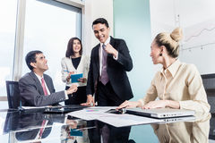 Group of businesswomen and businessmen negotiate contract Stock Photos