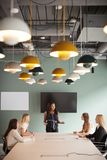 Group Of Businesswomen Sitting Around Boardroom Table And Collaborating On Task At Graduate Recruitment Assessment Day stock photo