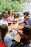 Group of smiling friends with tablets and phones, relaxing on a blurred background. Student life concept. Royalty Free Stock Photography