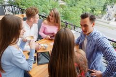 Group of smiling friends with tablets and phones, relaxing on a blurred background. Student life concept. Royalty Free Stock Photo