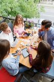 Group of smiling friends with tablets and phones, relaxing on a blurred background. Student life concept. Royalty Free Stock Photos