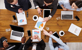 Group of busy business people meeting in office, top view. Business meeting top view. Multiethnic people work in office, above view of wooden table Royalty Free Stock Photos