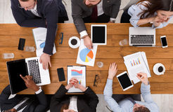 Group of busy business people meeting in office, top view. Business meeting top view. Multiethnic people work in office, above view of wooden table Royalty Free Stock Photography