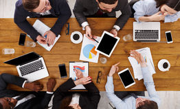 Group of busy business people meeting in office, top view. Business meeting top view. Busy people work in office, above view of wooden table with mobile phones Royalty Free Stock Photos