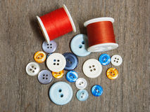 Group of buttons and needle reel on the wooden table Royalty Free Stock Photos