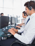 Group of call center employees working on computers Stock Photos
