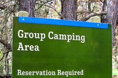 A group camping area sign indicating reservations are required.  stock photos