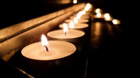 Group of candles on a base in a church stock image