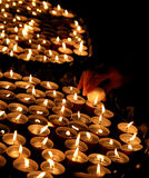 Group of candles lit in the church and the hand of the old woman Royalty Free Stock Photography