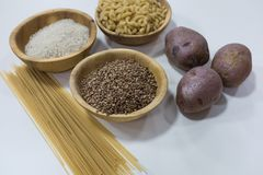 Group of carbohydrates for diet - bread, rice, potatoes and pasta on a wood table in the background.  stock photos