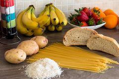 Group of carbohydrates for diet - bread, rice, potatoes and pasta on a wood table Stock Image
