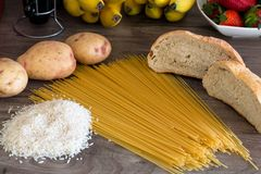 Group of carbohydrates for diet - bread, rice, potatoes and pasta on a wood table Royalty Free Stock Photo