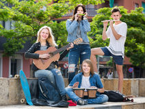 Group of carefree teenagers musicians. With instruments in park on summer day Royalty Free Stock Photos