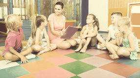 Group of careful children sitting with teacher Stock Images