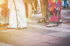 Group of casual men and women standing on paving. In a low angle view of their feet in sandals, jeans, shorts and caftans or long summer skirts, with the sun Royalty Free Stock Image
