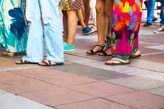 Group of casual men and women standing on paving. In a low angle view of their feet in sandals, jeans, shorts and caftans or long summer skirts, with foreground Royalty Free Stock Images