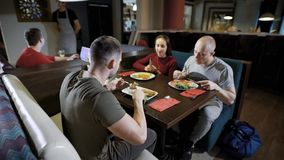 Young people dining together. Group of casual people relaxing in cafe together eating various food stock video