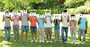 Group of casual young friends holding smiley faces over their faces stock video footage
