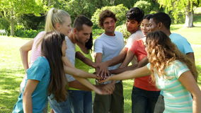 Group of casual young friends putting their hands together Royalty Free Stock Photos