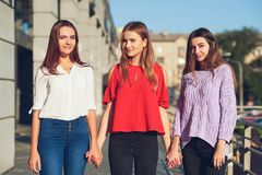 Group of casual young girls. Woman`s friendship. Youth fashion. Crop of diverse informal students standing in row outdoors urban background Stock Images
