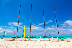 Group of catamarans with colorful sails on exotic Caribbean beach Royalty Free Stock Photos