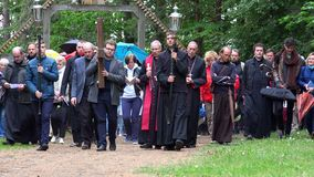 Group of catholic people and priests carry cross through cavalry way in forest. Vilnius, Lithuania - June 02, 2017: Group of catholic people and priests carry stock video footage