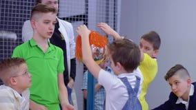 Group of caucasian boys explores van de graaff generator in scientific musem. Children and laboratory assistant make physical experiment with Van de Graaff stock video