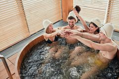 Group of caucasian diverse friends enjoying jacuzzi in hotel spa. Group of male and female friends visiting bathhouse in holidays, being overjoyed and happy stock image