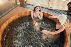 Group of caucasian diverse friends enjoying jacuzzi in hotel spa. High angle of two women visiting bathhouse in holidays, being overjoyed and happy, enjoying royalty free stock images
