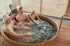 Group of caucasian diverse friends enjoying jacuzzi in hotel spa. High angle view of group of happy people young people having great time in spa, relaxing royalty free stock image
