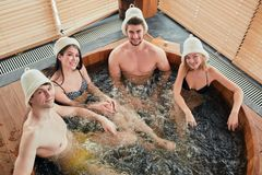 Group of caucasian diverse friends enjoying jacuzzi in hotel spa. High angle view of group of happy people young people having great time in spa, relaxing royalty free stock photos