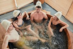 Group of caucasian diverse friends enjoying jacuzzi in hotel spa. High angle view of group of happy people young people having great time in spa, relaxing royalty free stock photography