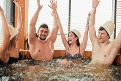 Group of caucasian diverse friends enjoying jacuzzi in hotel spa. Group of male and female friends visiting bathhouse in holidays, being overjoyed and happy royalty free stock images