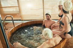 Group of caucasian diverse friends enjoying jacuzzi in hotel spa. Group of male and female friends visiting bathhouse in holidays, being overjoyed and happy royalty free stock image