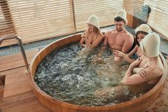Group of caucasian diverse friends enjoying jacuzzi in hotel spa. Two relaxing caucasian couples spend their day off in luxury spa centre, sharing ideas and news royalty free stock images