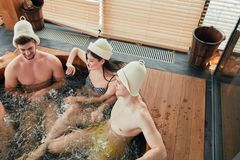 Group of caucasian diverse friends enjoying jacuzzi in hotel spa. Two relaxing caucasian couples spend their day off in luxury spa centre, sharing ideas and news stock images