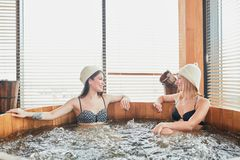 Group of caucasian diverse friends enjoying jacuzzi in hotel spa. Two relaxing girl spend their day off in luxury spa centre, sharing ideas and news while taking royalty free stock photography