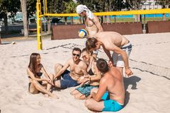 Group of caucasian friends resting at interval between sets on beach court. stock photo