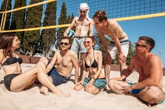 Group of caucasian friends resting at interval between sets on beach court. royalty free stock photography