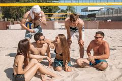 Group of caucasian friends resting at interval between sets on beach court. stock image