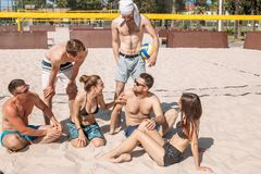 Group of caucasian friends resting at interval between sets on beach court. royalty free stock image