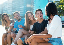 Group of caucasian and hispanic young adults has fun. Outdoor in the city in the summer Stock Photos