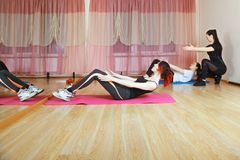 Group abs training. Group of caucasian women training abdominal muscles. Trainer explains exercise. Horizontal shot Stock Photography