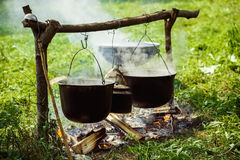 A group of cauldrons and kettle are hanged upon fire. At tourist camp at green summer outdoors background Stock Photos
