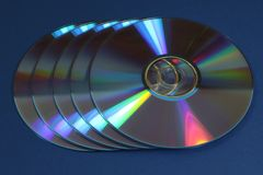 A group of CDs or DVDs. On a blue background royalty free stock photos