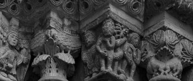 Group of characters on the capitals. Shot and black and white, detail on the sculpture on the facade of this historic building representing some plants / flowers Royalty Free Stock Image