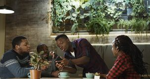 Young man sharing interesting story with friends. Group of cheerful African-American people listening to young men telling story expressively while chilling in Royalty Free Stock Image