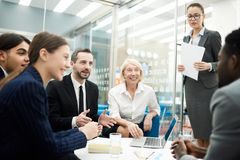 Briefing in Office. Group of cheerful business people brainstorming ideas for startup project sitting at coffee table in office, copy space stock photography