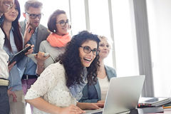 Group of cheerful businesspeople with laptop at desk in creative office stock photo