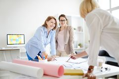 Group of Female Designers Collaborating. Group of cheerful businesswomen discussing work while collaborating on design project in studio royalty free stock photos